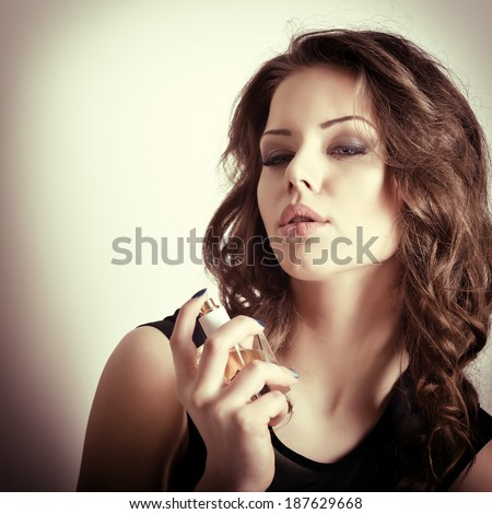 Girl with perfume, young beautiful woman holding bottle of perfume and smelling aroma, toned soft beige.