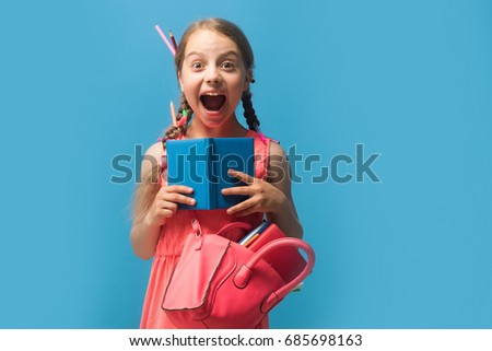 Girl with pink bag holds open blue notebook. Pupil with long braids, isolated on blue background. Back to school and childhood concept. Kid with happy or surprised face and colored pencils in hair #685698163