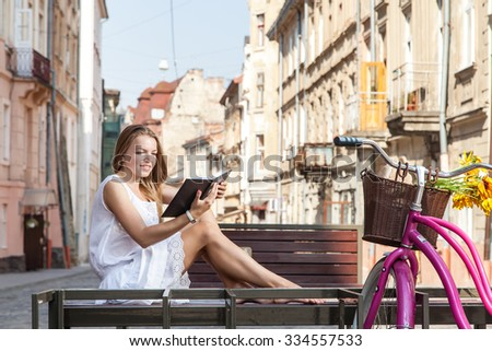 girl with pink bicycle and grocery basket sitting on street bench and reading book