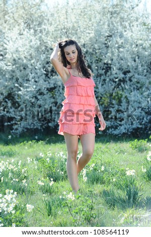 girl with pink dress walking in a field of daisies