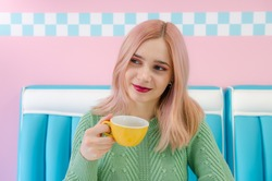 Girl with pink hair drinking tea in a cafe