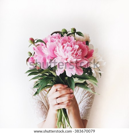 Girl with pink peonies bouquet at white wall
