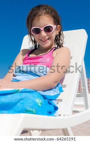 Girl with pink sunglasses relaxing in a deck chair