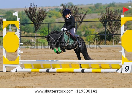Girl with pony in jumping show