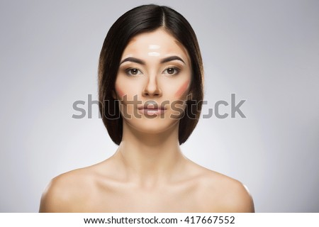 Girl with professional contour and highlight makeup. Contouring face make-up applying sample. Hair at the back. Beauty portrait, head and shoulders, full face. Indoor, studio