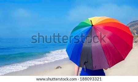 Girl with rainbow umbrella by the ocean