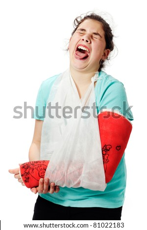 Girl with red cast and sling bandage, has pain and holds her broken arm, studio shot against a white background.