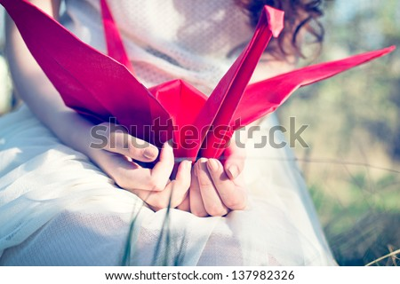 Girl with red origami crane