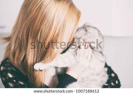 girl with redheads hair playing with a gray cat #1007188612
