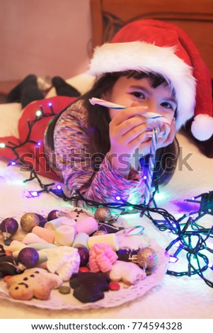 girl with santa hat eating christmas candy with christmas lights