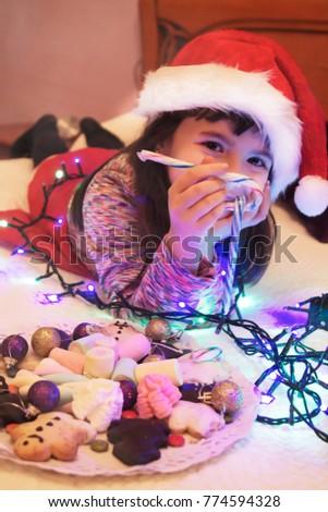 girl with santa hat eating christmas candy with christmas lights