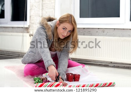 Girl with scissors preparing gifts for party