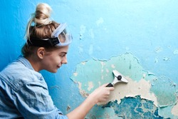 Girl with scraper in hand peels off a layer of cracked blue paint on the wall in the apartment, woman makes repairs