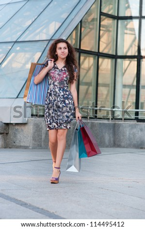 girl with shopping bags goes around glass building