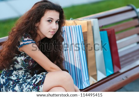 girl with shopping bags on the bench