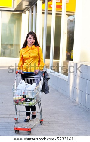 girl with shopping trolley going from shop to car