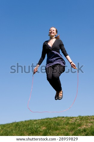 girl with skipping rope on a green meadow