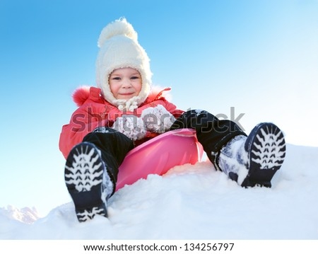 Girl with sleds on the hill against the blue sky