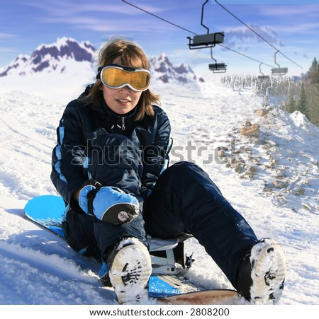 girl with snowboard over the mountain background