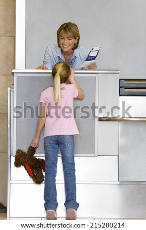 Girl , with soft toy, talking to female check-in attendant at airport check-in area, woman holding boarding passes, smiling, rear view