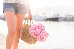Girl with straw bag and pink flowers hydrangea. Traveler has vacation in sea resort near yacht port at sunset with light background.