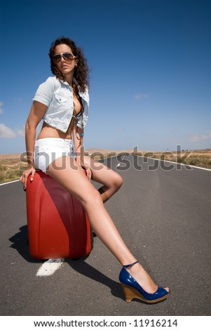 girl with suitcase stops the car on road