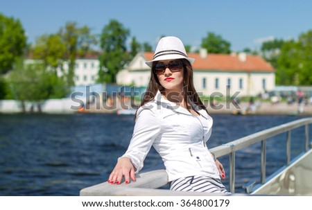 Girl with sunglasses sitting on white yacht #364800179