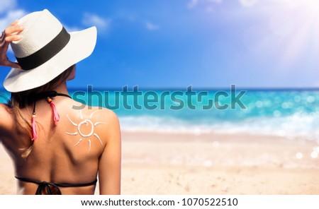 Girl With Suntan Lotion Shaped Sun In The Beach #1070522510