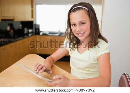 Girl with tablet sitting at the kitchen table