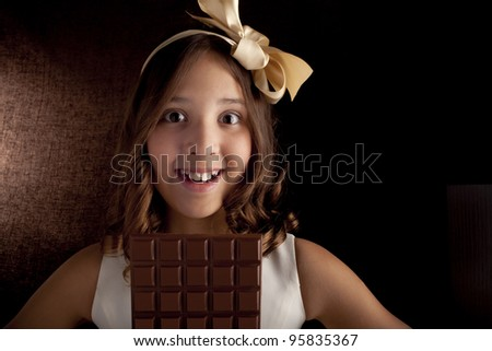 girl with the big chocolate  and with  bow on a head looking at camera
