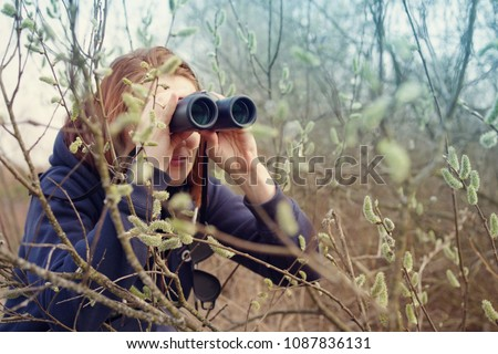 Girl with the binoculars against the background of the nature. Observation of birds. Birdwatching