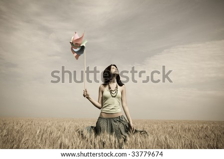 Girl with toy wind turbine at field, photo in age style