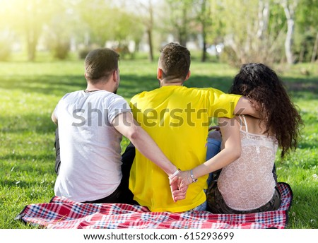 Girl with two boys, one hugging her and another one holding her hand behind his back. Love triangle #615293699
