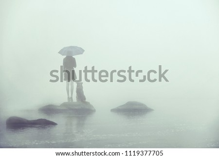 Girl with umbrella and dog standing on a little island in the middle of the water. Lonely in the fog