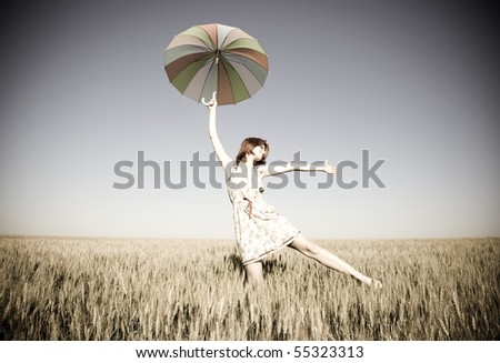 Girl with umbrella at field. Photo in old image style. - stock photo