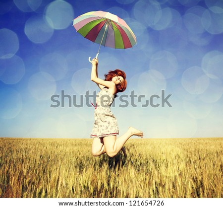 Girl with umbrella at field. Photo with bokeh at background.