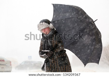 Girl with umbrella during snow storm