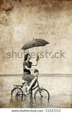 Girl with umbrella on bike. Photo in old image style.