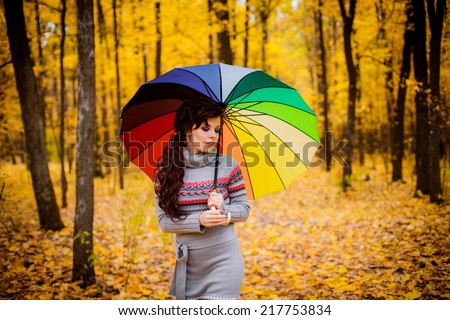 girl with umbrella rainbow colors. autumn forest. Outdoors