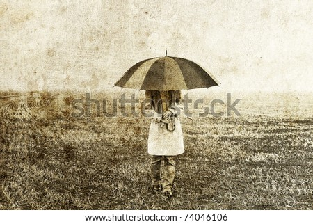 Girl with umbrella staying on field. Photo in old image style.