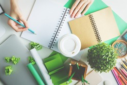 Girl with various creative green items on desktop writing in spiral notepad