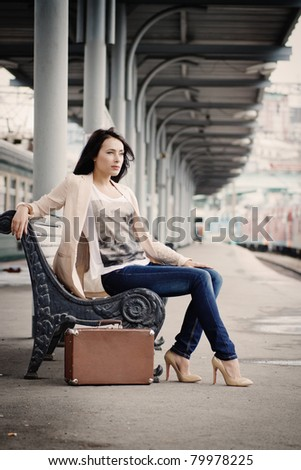 girl with vintage suitcase sits on the ramp