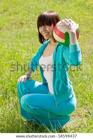 girl  with volleyball  in  summer park  smiling