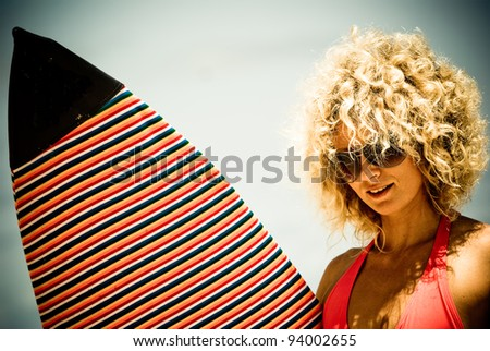 girl with white hair posing with surf on the shore of the island of Mauritius