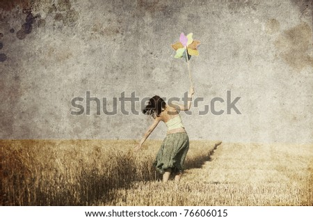 Girl with wind turbine at wheat field. Photo in old color image style.