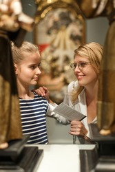 Girl with woman in glasses looking with interest at ancient sculptures in museum, using guidebook