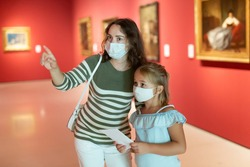 Girl with woman in masks looking with interest at painting in the museum, using guidebook