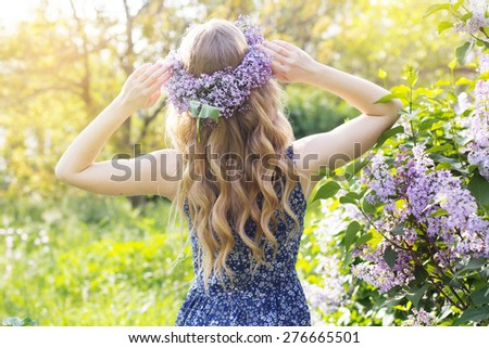 Girl with wreath from lilac purple flowers in green park, spring time