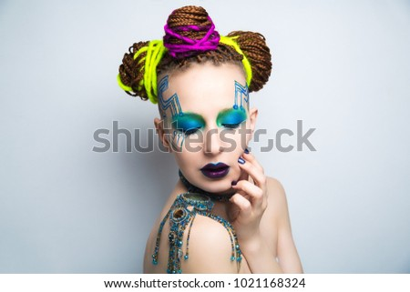 Stock Photo Girl woman creative make-up, lines motherboard painted on her face. Long fingers with manicure. Purple violet lips, eyes lenses, colored blue green shadows. Hair dreadlocks braided, neon yellow string