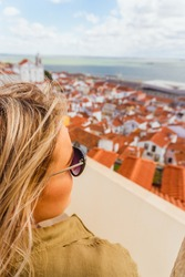 Girl woman looks over roof tops with blonde hair and sunglasses on; spring day in Lisboa on spring break in Europe